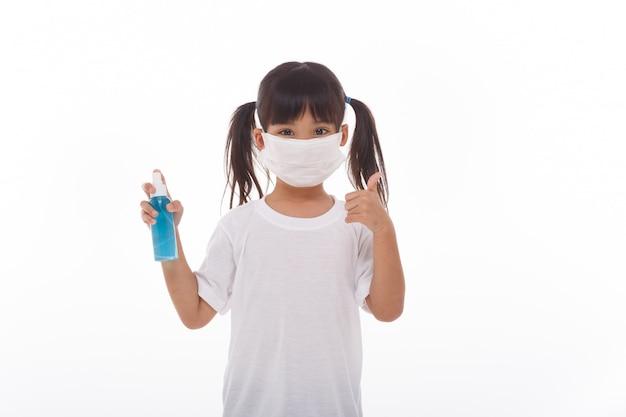 Nettes asiatisches mädchen, das eine maske trägt und alkoholgel hält