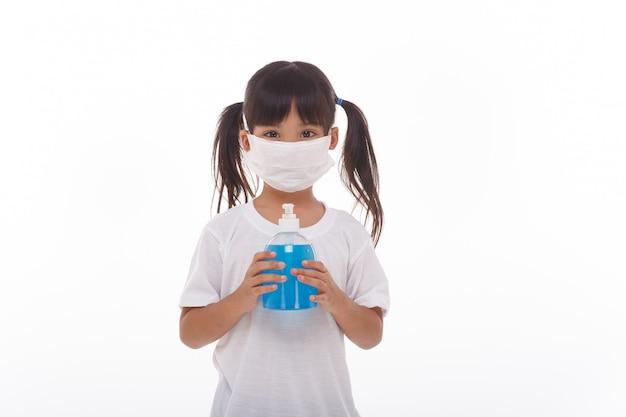 Nettes asiatisches mädchen, das eine maske trägt und ihre hände mit alkohol wäscht