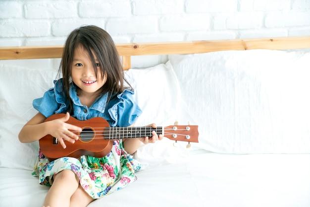 Nettes asiatisches mädchen, das gitarrenukulele in ihrem haus spielt