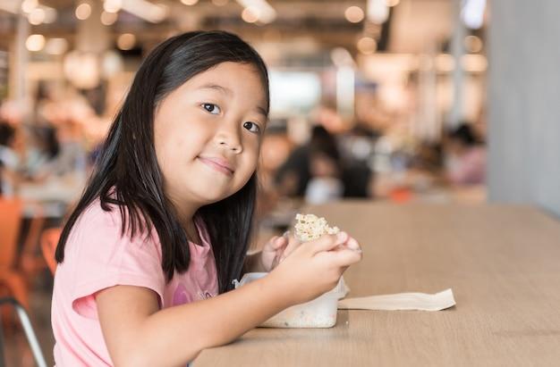 Nettes asiatisches mädchen, das kastenmittagessen im gastronomiebereich, fastfood-konzept isst