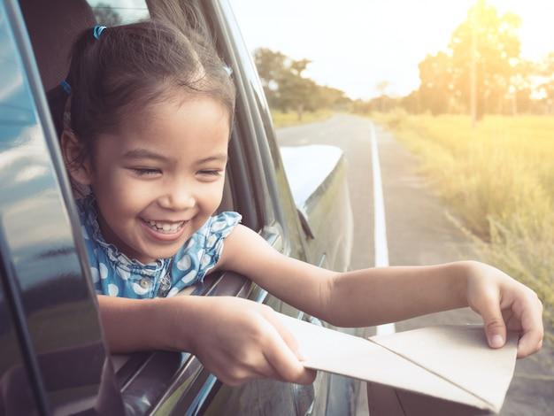 Nettes asiatisches mädchen des kleinen kindes, das spaß hat, mit spielzeugpapierflugzeug aus autofenster heraus zu spielen