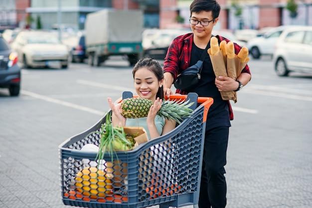 Nettes asiatisches mädchen hält ananas und sitzt im einkaufstablett mit essen, während vietnamesischer junge es zu ihrem auto auf dem parkplatz nahe einkaufszentrum schiebt.