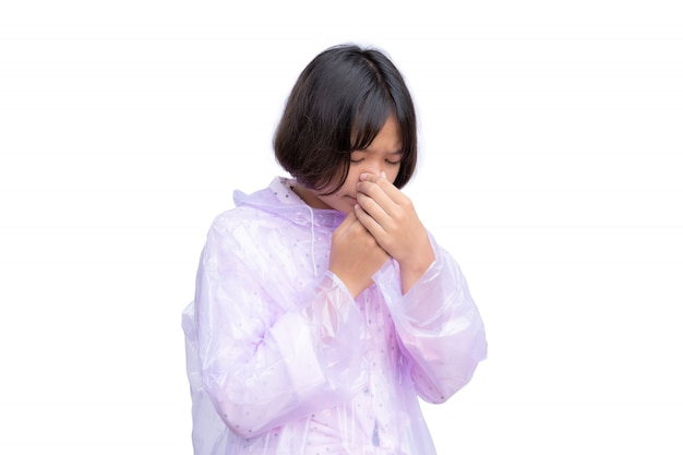 Nettes asiatisches mädchen im regenmantel husten auf weiß
