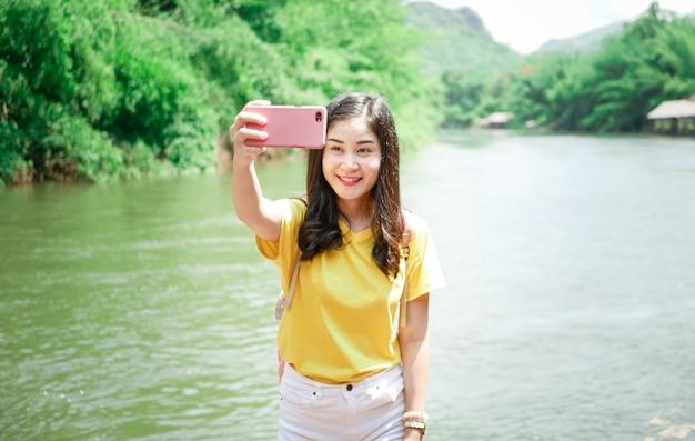 Nettes asiatisches mädchen, in einem gelben t-shirt und in einem rosa rucksack, auf ihrer reise, lächelte sie, nahm ein selfie und warf in vielen augenblicken mit grünem naturplatz auf.