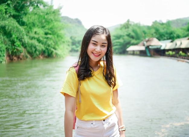 Nettes asiatisches mädchen, in einem gelben t-shirt und in einem rosa rucksack, auf ihrer reise, lächelte sie und warf in vielen augenblicken mit grünem naturplatz auf.