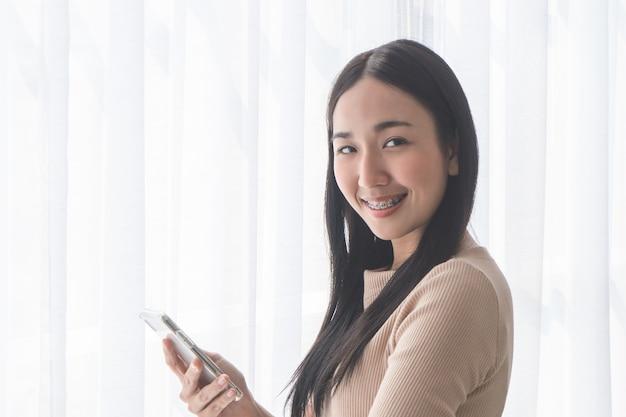 Nettes asiatisches mädchen mit klammern unter verwendung des handys durch morgenfenster