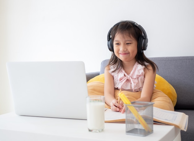 Nettes asiatisches mädchen verwenden notizbuchcomputer für das lernen der online-lektion während der quarantäne zu hause. online-bildung und soziales distanzkonzept.