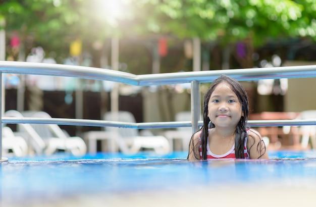 Nettes asiatisches mädchenspielwasser im swimmingpool