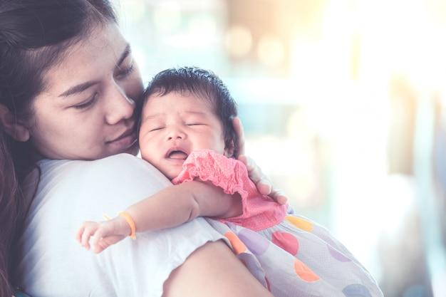 Nettes asiatisches neugeborenes baby, das auf der schulter der mutter schläft.