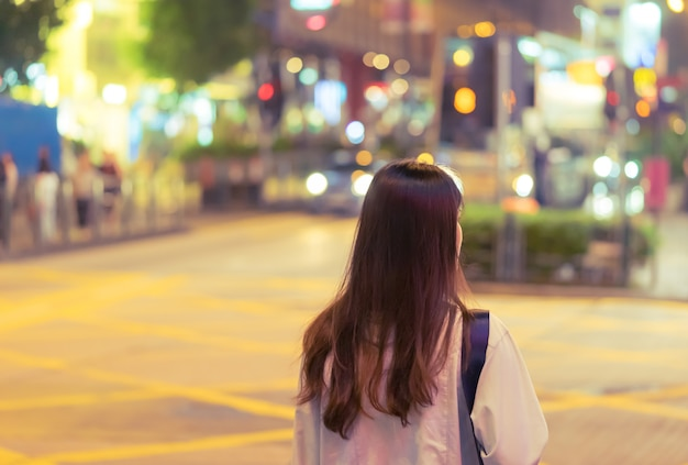Nettes asiatisches reisendmädchen in der nachtstraße von hong kong
