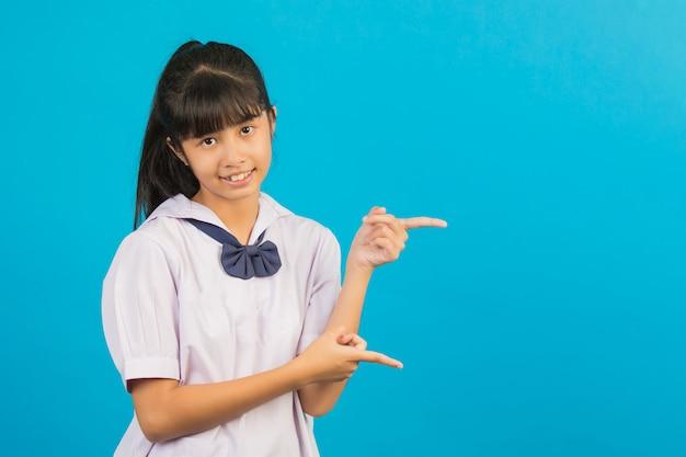 Nettes asiatisches schulmädchen, das zwei hände zeigen geste auf einem blau tut.