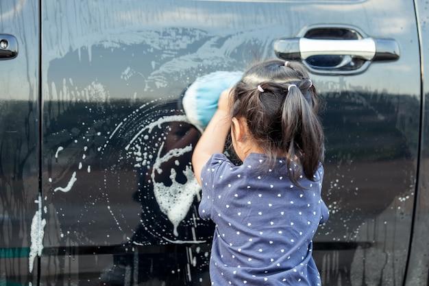 Nettes asiatisches waschendes auto des kleinen mädchens