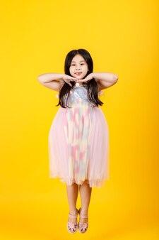 Nettes asiatisches weibliches kind posieren zur kamera mit selbstbewusstem auf gelbem hintergrund.