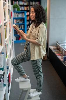 Nettes asiatisches weibliches studentenlesebuch von bookshelf
