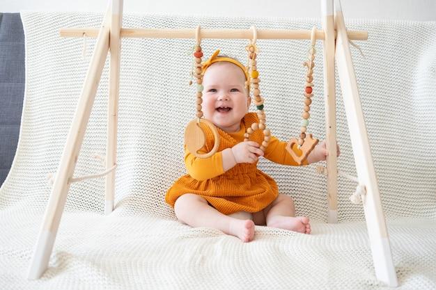 Nettes aufgeregtes baby, das griff mit holzspielzeug-kleinkindtrainer spielt, der auf der couch sitzt