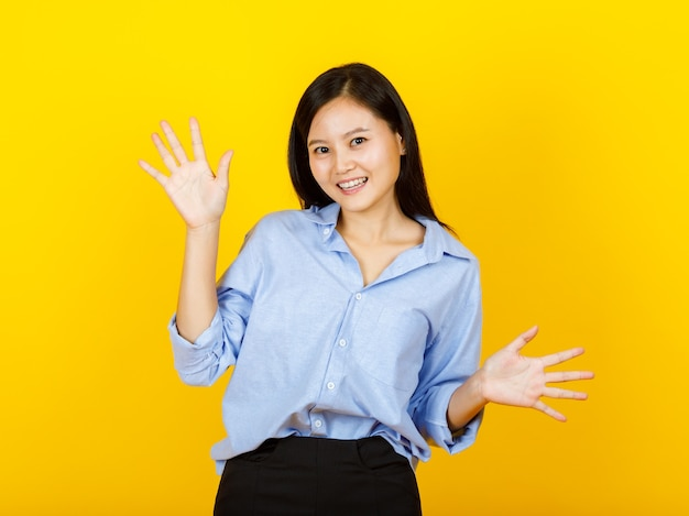 Nettes ausschnittporträt einer schönen asiatischen frau, die ein lässiges langarmhemd als lustige chefsekretärin trägt, lächelt und handgesten spielt, um 10 überraschte geschäftsförderung und glückliches geschäft auszudrücken