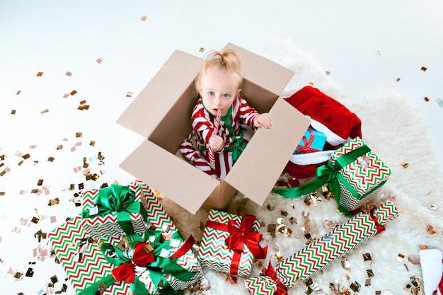 Nettes baby 1 jahr alt, das im kasten über weihnachtsdekorationshintergrund sitzt. urlaub, feier, kinderkonzept