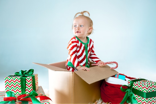 Nettes baby 1 jahr alt, das im kasten über weihnachtshintergrund sitzt. urlaub, feier, kinderkonzept