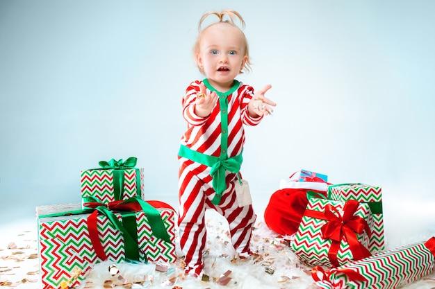Nettes baby 1 jahr alt, das weihnachtsmannmütze trägt, der über weihnachten aufwirft