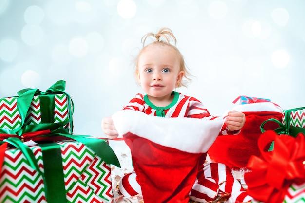 Nettes baby 1 jahr alt, das weihnachtsmütze trägt, der über weihnachtsdekorationen aufwirft