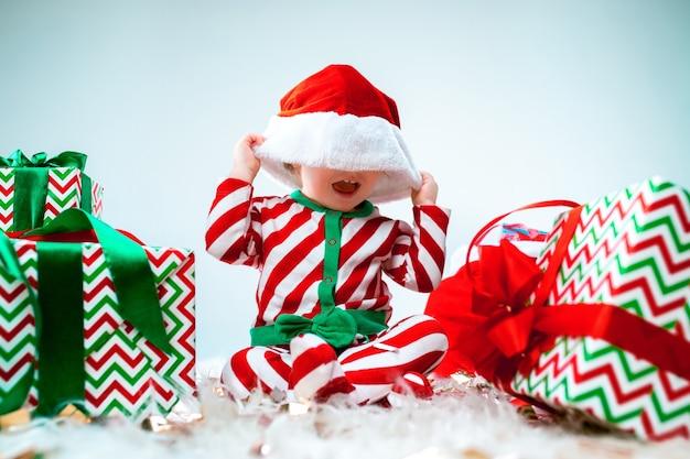 Nettes baby 1 jahr alt, das weihnachtsmütze trägt, der über weihnachtsdekorationen mit geschenken aufwirft. mit weihnachtskugel auf dem boden sitzen. ferienzeit.