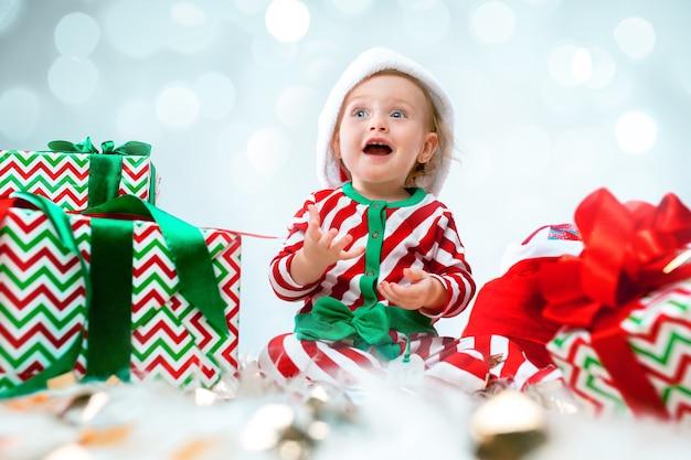 Nettes baby 1 jahr alt, das weihnachtsmütze trägt, der über weihnachtsdekorationen mit geschenken aufwirft. mit weihnachtskugel auf dem boden sitzen
