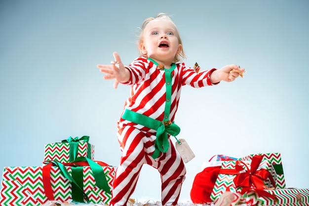 Nettes baby 1 jahr alt, das weihnachtsmütze trägt, der über weihnachtshintergrund aufwirft. mit weihnachtskugel auf dem boden stehen. ferienzeit.