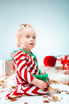 Nettes baby 1 jahr alt nahe weihnachtsmütze, die über weihnachten aufwirft