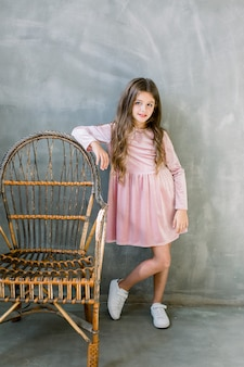 Nettes baby 5-6 jahre alt, das stilvollen rosa kleid übergrünen hintergrund trägt. kamera betrachten. geburtstagsfeier. feier.
