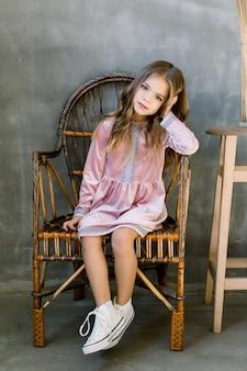 Nettes baby 5-6 jahre alt, das stilvolles rosa kleid sitzt, das auf der übergrauen wand des holzstuhls sitzt. geburtstagsfeier. feier.