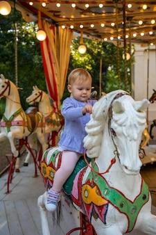 Nettes baby auf dem pferd des alten retro-karussells prag tschechien