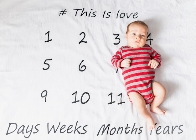 Nettes baby auf gestreiftem körper mit kalender