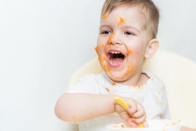 Nettes baby beim essen schmierte sein gesicht mit einem kürbis