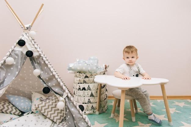 Nettes baby, das am tisch im kinderzimmer in weiß-, grau- und blautönen sitzt. in der nähe des tipis und einer tüte spielzeug