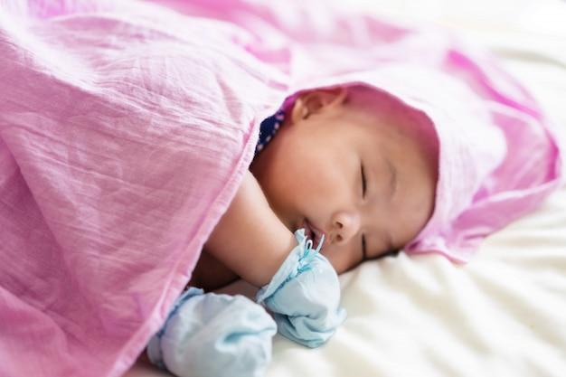 Nettes baby, das auf bett legt neugeborenes schlafen zwei monate. säugling