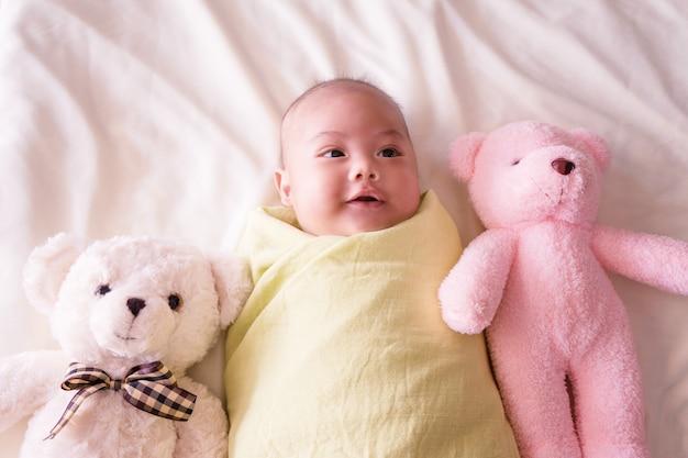 Nettes baby, das auf bett legt neugeborenes schlafend mit teddybär. zwei monate