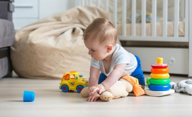 Nettes baby, das auf dem boden krabbelt und mit spielzeugauto spielt
