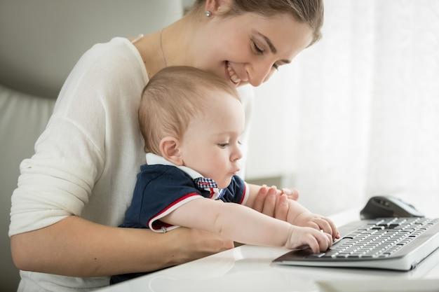 Nettes baby, das auf dem schoß der mutter sitzt und auf der tastatur tippt