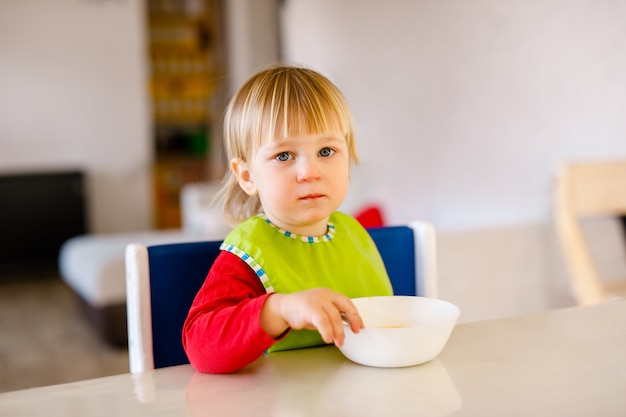 Nettes baby, das auf hohem kinderstuhl sitzt und gemüse allein in der weißen küche isst.