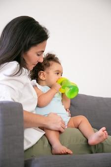 Nettes baby, das auf mutterschoß sitzt und wasser von flasche trinkt. vertikaler schuss. elternschafts- und kindheitskonzept