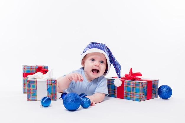 Nettes baby, das auf seinem magen in einer kappe des neuen jahres unter weihnachten liegt