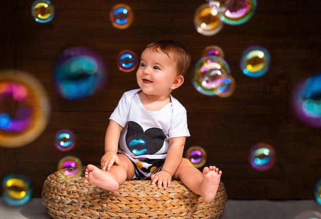 Nettes baby, das auf strohstuhl sitzt und seifenblasen auf hölzernem hintergrund betrachtet