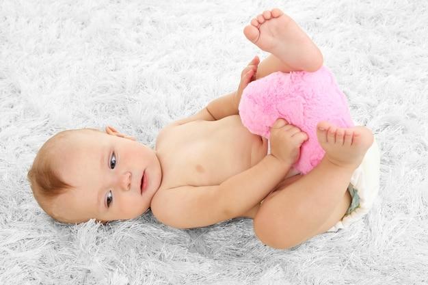 Nettes baby, das auf teppich im zimmer liegt
