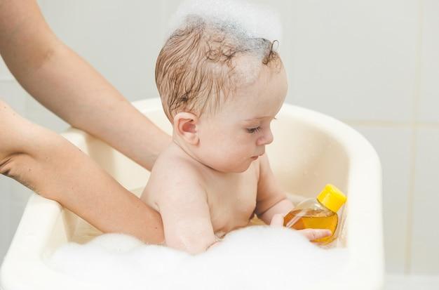 Nettes baby, das bad nimmt und mit spielzeug spielt
