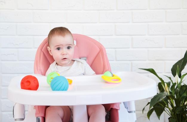 Nettes baby, das eine rassel im stuhl spielt. draufsicht