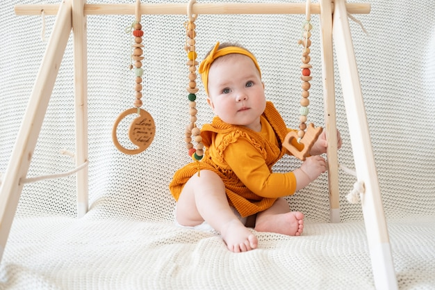 Nettes baby, das griff mit holzspielzeug-kleinkindtrainer spielt, der auf der couch sitzt hold