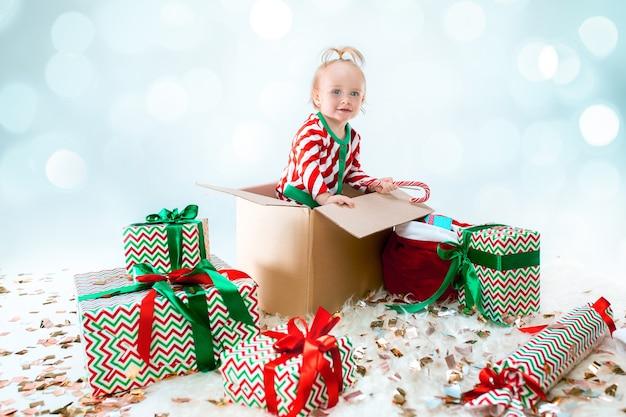 Nettes baby, das im kasten über weihnachtshintergrund sitzt. urlaub, feier, kinderkonzept