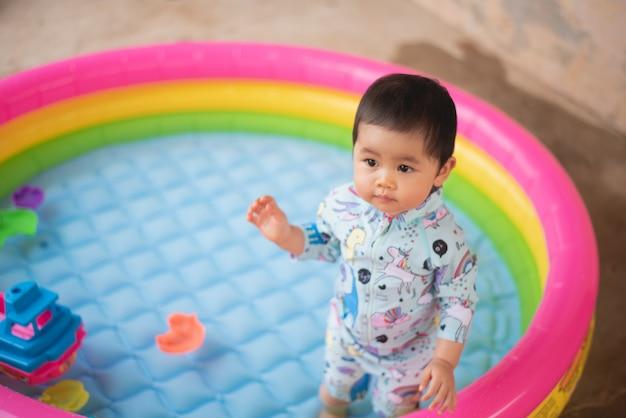 Nettes baby, das im kleinen pool schwimmt