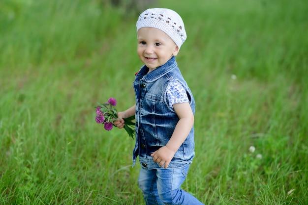 Nettes baby, das im schönen park mit bunter blume auf sommersaison geht, die er lächelt und glücklich stehenden naturhintergrund im freien steht.