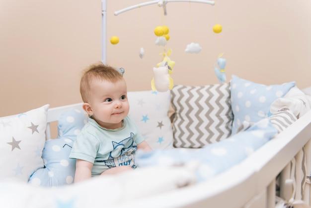 Nettes baby, das in einem weißen runden bett sitzt. leichter kindergarten für kleine kinder. spielzeug für kinderbett. lächelndes kind, das mit handy des filzes im sonnigen schlafzimmer spielt.
